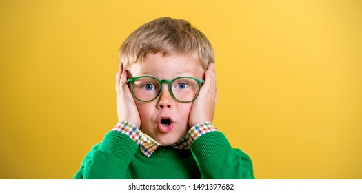 Portrait of school boy in glasses with funny shocked face expression isolated on yellow background. Back to school.