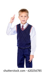 Portrait of a school boy raising his index finger, drawing attention. Educational concept. Isolated over white background.