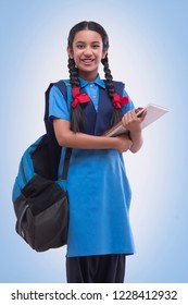 Portrait of school girl in uniform holding book and bag