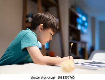 Portrait of school kid boy siting on table doing homework, Child boy holding pencil writing on paper, Homeschooling concept