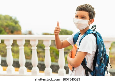Portrait of of School kid wearing protective face mask for pollution or virus and showing thumbs up. Coronavirus and school concept