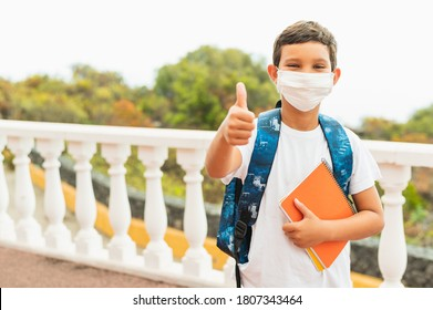 Portrait of of School kid wearing protective face mask for pollution or virus and showing thumbs up while waiting for school bus in the morning. Coronavirus and school concept.