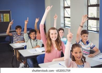 Portrait of school kids raising hand in classroom at school