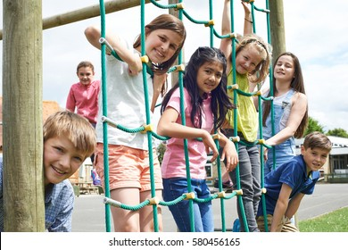 Portrait Of School Pupils Playing On Climbing Frame
