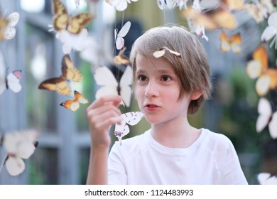 Portrait of a school-age child in the setting of paper butterflies