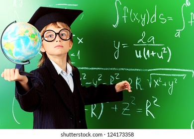 Portrait of a schoolboy in big round spectacles and academic hat at a classroom.