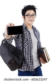 Portrait of a schoolboy carrying a backpack and books while showing blank screen of a smartphone, isolated on white background