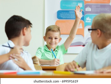 Portrait of schoolboy raises his hand in school at the lesson