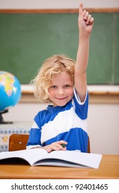 Portrait of a schoolboy raising his hand in a classroom
