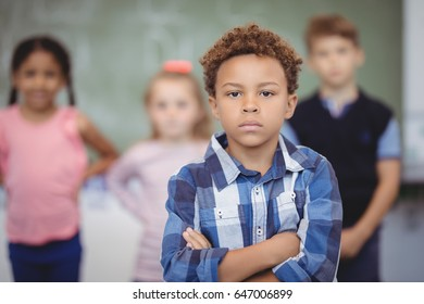 Portrait of schoolboy standing with arms crossed in classroom at school