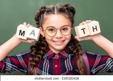 portrait of schoolchild holding wooden cubes with word math near blackboard