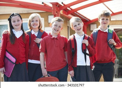 Portrait Of Schoolchildren Outside Classroom Carrying Bags