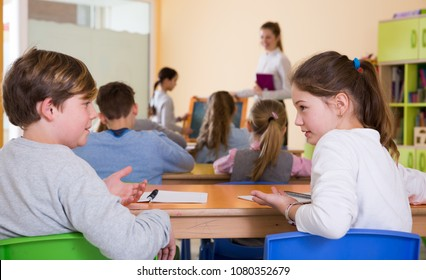Portrait of schoolchildren sitting in classroom and chatting during lesson