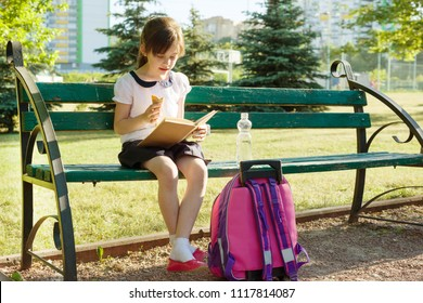 Portrait of schoolgirl 7 years old on a bench reading book, eating ice cream. Background school yard.
