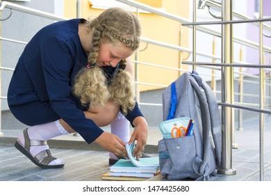 Portrait of a schoolgirl.  Concept  school days, Back to school.  girl in a  uniform. teenager examines accessories, backpack. pupil, learner, scholar