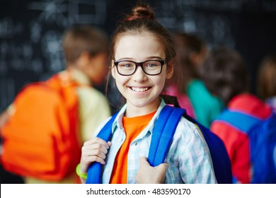 Portrait of schoolgirl in glasses smiling at camera