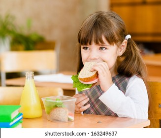 portrait schoolgirl looking at camera while having lunch during