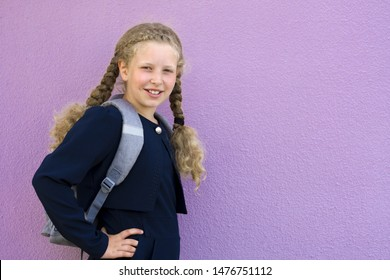 Portrait of a  schoolgirl on the background. Concept  school days, Back to school. girl in a  uniform with a backpack. pupil, learner, scholar