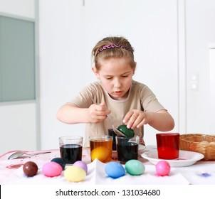 Portrait of schoolgirl painting Easter eggs
