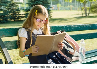 Portrait of schoolgirl primary school with backpack on a bench reading book, background school yard.