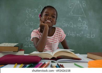Portrait of schoolgirl reading book in classroom