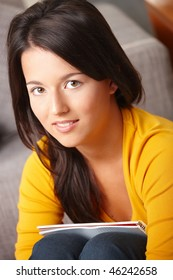 Portrait of schoolgirl sitting with exercise book in lap looking at camera.