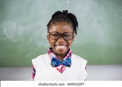 Portrait of schoolgirl smiling in classroom at school