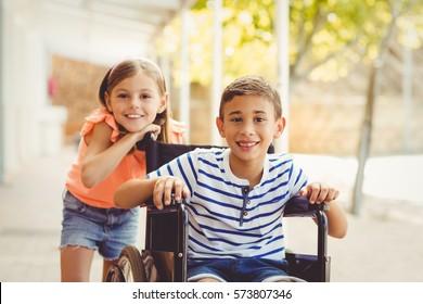 Portrait of schoolgirl standing with schoolboy on wheelchair in school corridor