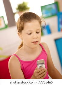 Portrait of schoolgirl using cellphone at home?