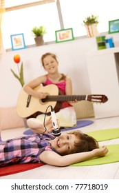 Portrait of schoolgirls playing music, one singing with microphone, other playing guitar, smiling.?