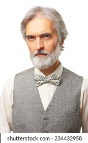 Portrait of scowl suspicious aged caucasian man with a grey beard and bowtie isolated on white background