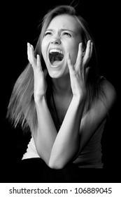 Portrait of screaming girl on black background