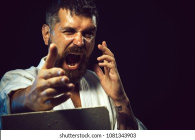 Portrait of screaming karate master instructor. Strong, angry, bearded man dressed in kimono portrait screaming boxer. Karate man breaking with hand concrete brick. Handsome aikido fighter. Copy space