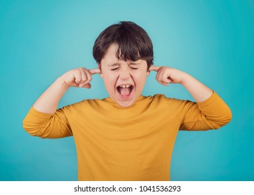 portrait of a Screaming little boy child covering ears with hands