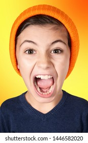 portrait of screaming young boy with big head on orange background