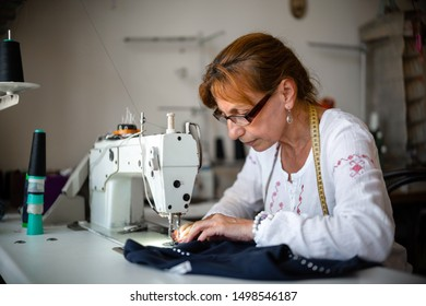 Portrait of a seamstress working in her sewing studio
