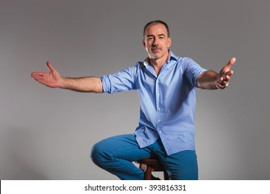 portrait of seated casual man welcoming with open arms while looking at the camera in gray studio background