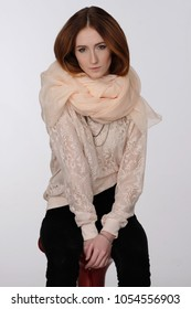 Portrait of a seated red-haired girl on a light gray background. She is dressed in an elegant lace blouse and a light scarf around her neck. Warm colors, gold ornaments. Fashion.