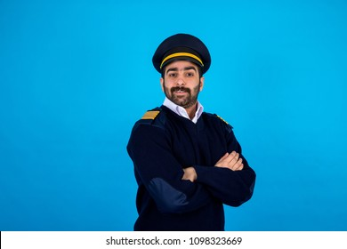 Portrait of a security man wearing his uniform, standing crossed arms and smiling, standing on a blue background