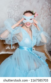 Portrait of a seductive beautiful woman in a retro interior and boudoir dress and with a blue mask.