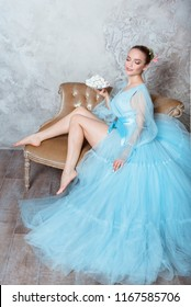 Portrait of a seductive beautiful woman in a retro interior and a boudoir dress, holds a plate with sweets in a bowl.
