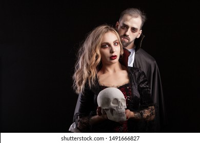 Portrait of seductive couple dressed up like vampires for halloween carnival. Man in Dracula costume. Sexy vampire woman holding a human skull.