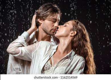 portrait of seductive couple hugging under rain isolated on black