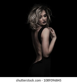 portrait of seductive elegant woman with messy blonde hair looking down while holding her shoulder, standing on black background