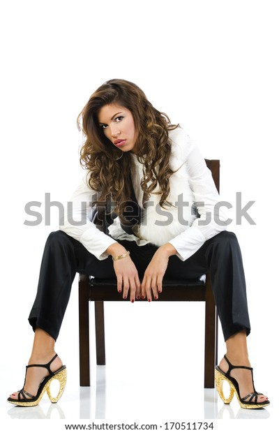 Portrait of a seductive girl sitting in the chair, on white background