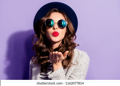 Portrait of seductive tempting girl sending air kiss at camera with pout lips palm having red pomade modern hairdo isolated on violet background expressing feeling to boyfriend