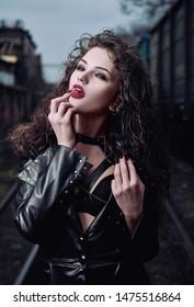 Portrait of a seductive vamp woman (informal model) dressed in leather coat