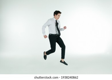 Portrait of self-confidence young and handsome Asian businessman executive looked in shirt and tie jumping high and freeze stop in air, copy space studio shot isolated on white background.