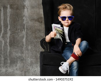 Portrait of self-confident rich kid boy millionaire siting in luxury armchair with bundles of dollars cash in his hand free text copy space. Going to buy everythimg or bribe