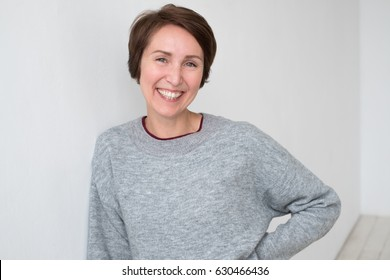 Portrait of self-confident woman in casual clothing style. She smiles broadly. Positive emotions.